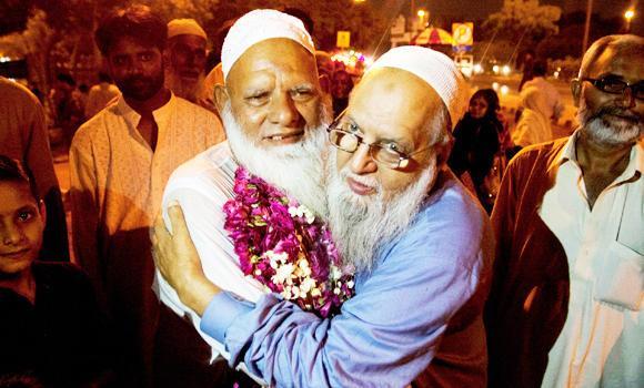 A man receives his family member who returned from Saudi Arabia after the Haj pilgrimage at Karachi airport, Pakistan.