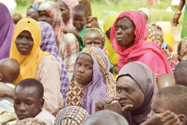 Women who were rescued after being held captive by Boko Haram, sit as they wait for medical treatment at an internal displaced person's camp near Mubi, northeast Nigeria.